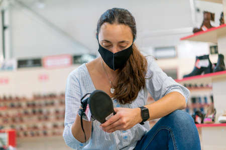 woman wearing face protective medical mask for protection from virus disease in shoes store during pandemic. Woman during a pandemic