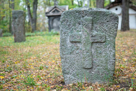 A worn sandstone grave marker in the shade on a very bright day. There is no text visible on the stone, but there is some moss on the top. Tombstone and graves in an ancient church graveyard 免版税图像