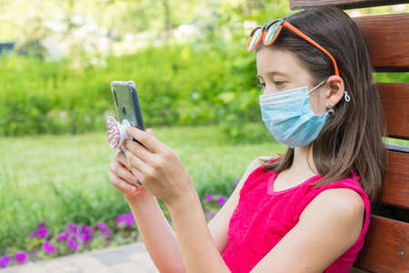 girl in protective mask holding a smartphone. teen girl siting on bench in green park with mobile phone. First stage of loosening virus restrictions and self-isolation Reklamní fotografie