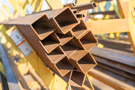 stack of steel pipe and metal beams on rack. metal pipes, profiles, rods, corners, rails, a choice of metal products. Metal shop 免版税图像