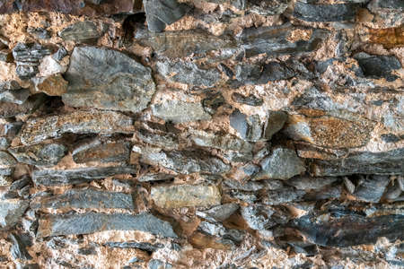 Ancient stone wall of the castle basement. Wall texture of ancient old brick stone. Outdoor exterior castle facade with destroyed uneven pattern of shabby rock. Solid wall sandstone structure
