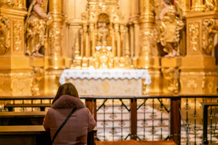 A woman in a temple prays to God. Woman praying in front of altar. Praying woman in front of altar. selected focus 免版税图像
