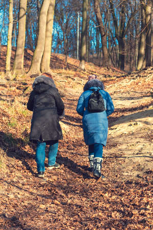 Two girls go uphill. Woman hiking through green woods vegetation, going uphill. Tourism and travel concept