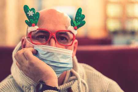 Bald man in funny glasses wearing surgical mask and protective gloves due to pandemic. Holding a Christmas gift box for home delivery. toned 免版税图像