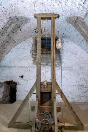 Ancient guillotine in the basement of the castle. Tool to apply the death penalty: the guillotine 免版税图像