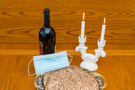 Dust mask, bottle of wine and matzah - a traditional Jewish food for Passover. 免版税图像 - 164346932
