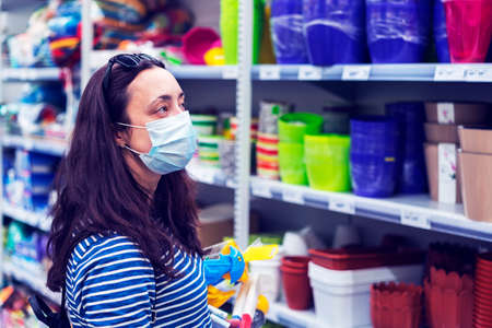 Woman in medical mask choosing goods in a store. Concept of shopping during quarantine at pandemic.