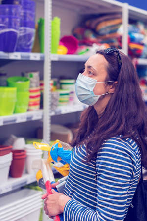 Woman in medical mask choosing goods in a store. Concept of shopping during pandemic 免版税图像