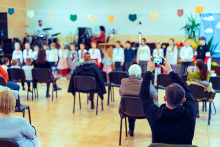 Parents at the performance of children in kindergarten or school. Children on stage. Many parents are watching the kids performance in the hall during Chistmas holiday, blurry