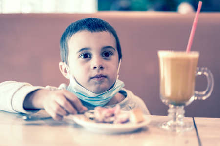 Little boy in a medical mask in a cafe eats a cake. A child wearing a mask in a cafe during a pandemic. toned