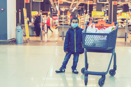 Boy wears protected mask in store. Shopping time during virus outbreak. Boy in a medical mask. Shopping with kids during virus outbreak. Boy in face mask in supermarket. toned