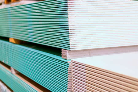 Pallet with Drywall sheets plasterboard in the building warehouse store. Stacking of white gypsum panels, drywall or plasterboard. Gypsum plasterboard in the pack. toned 免版税图像
