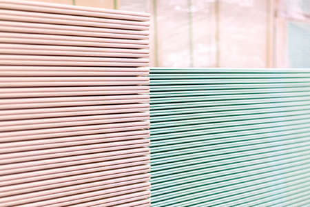 Pallet with Drywall sheets plasterboard in the building warehouse store. Stacking of white gypsum panels, drywall or plasterboard. Gypsum plasterboard in the pack