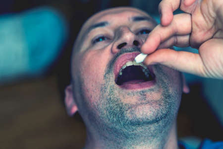 Extreme closeup man face taking white pill, mouth view swallowing pills, illness. man take medicine,open mouth and bring medicine to mouth. toned. selected focus
