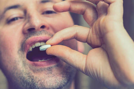 Extreme closeup man face taking white pill, mouth view swallowing pills, illness. man take medicine,open mouth and bring medicine to mouth. toned