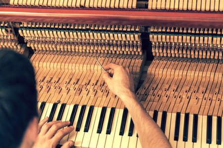 Piano tuning process. closeup of hand and tools of tuner working on grand piano. Detailed view of Upright Piano during a tuning. toned.