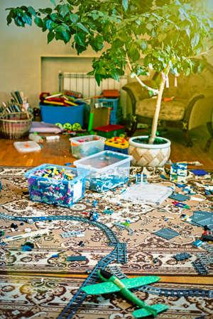 Games floor for preschoolers kindergarten. interior children's room. mess in the room. mess in the children's room, scattered toys, boxes on the floor. toned. vertical photo.