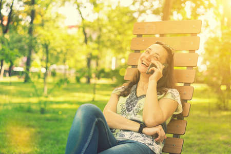 Young beautiful smiling woman talking on cell phone. Beautiful young female sitting on a park bench and talking on the phone. beautiful woman sitting on the park bench. toned 免版税图像