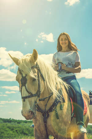 the rider on the white horse. Young horsewoman riding on white horse, outdoors view. girl on white horse runs free. toned. 免版税图像