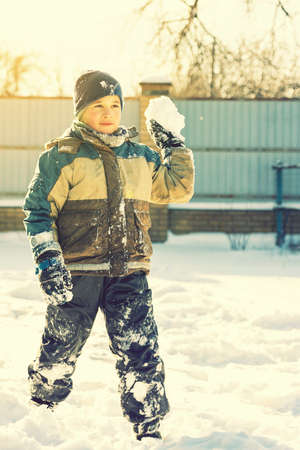 Baby boy walking at snowfall. Child in winter clothes playing with snow. boy making snowball outdoor. Boy playing snowballs in winter park. Christmas winter fun. toned.