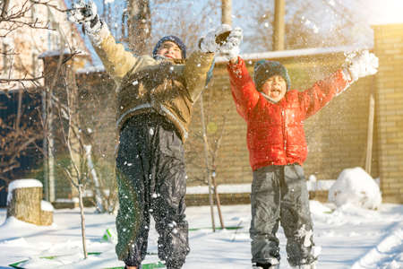 Two boys play with snow. Happy childhood. Brothers on a walk. two kids playing with snow. toned. 免版税图像