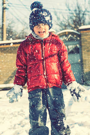 Excited Child playing with snow on white snow background. smiling boy catching snowflakes. Funny little boy in blue winter clothes walks during a snowfall. Outdoors winter activities for kids. toned. 免版税图像 - 164321097