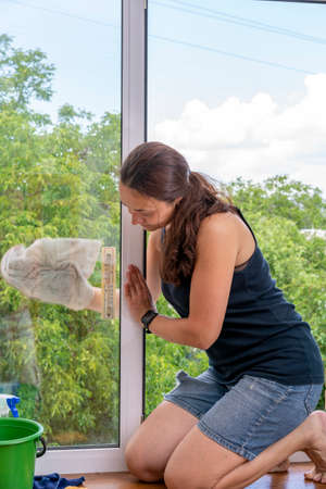Beautiful woman cleaning window at home. A girl washes windows at home. To clean up the house. Long-haired woman cleaning windows with spray in home. toned.