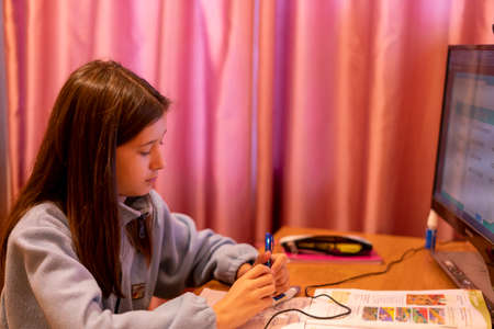 Smart preteen schoolgirl doing her homework with digital tablet at home. Child using gadgets to study. Education and learning for kids. Homeschooling during quarantine. toned. selected focus. 免版税图像