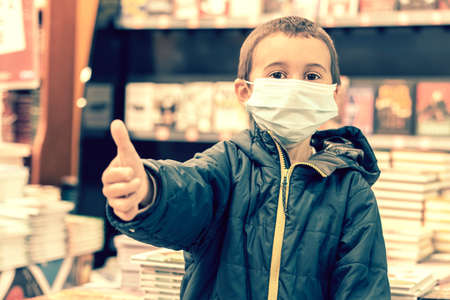 Boy in medical mask at bookstore. young boy chooses books in a bookshop. boy wear a protective mask In a bookstore. Concept of life And protect yourself from the outbreak. toned.