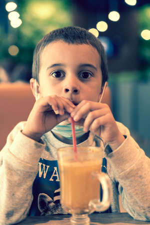 A child wearing a mask in a cafe during a pandemic. A boy in a cafe drinks sea buckthorn tea in a cafe during a pandemic. toned.