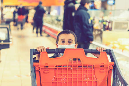 Child wearing surgical face mask buying fruit in supermarket in pandemic. little boy in a supermarket is wearing a medical mask. quarantine. toned.