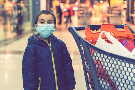 Boy wears protected mask in store. Shopping time during outbreak. Boy in a medical mask. Shopping with kids during virus outbreak. Boy in face mask in supermarket. toned. 免版税图像