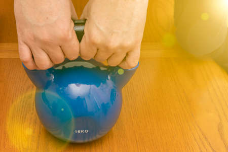 Iron kettlebell in the man's hand on a wooden background. Close up. Sports kettlebell in the gym, top view. kettlebells on gym. Close up. Sports kettlebell in the gym, top view. toned. 免版税图像