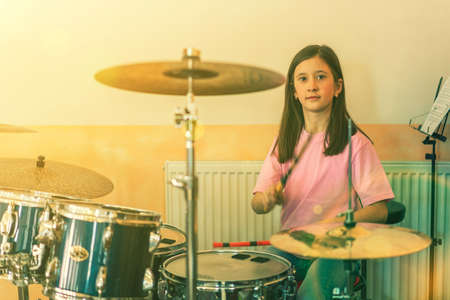 Happy girl in music therapy by playing drum kit on music room. Beautiful young girl drummer with drumsticks playing drums and cymbals. Female drummer. toned. 免版税图像