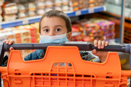 Boy wears protected mask in store. Shopping time during virus outbreak. Boy in a medical mask. Shopping with kids during virus outbreak. Boy in face mask in supermarket. toned. 免版税图像