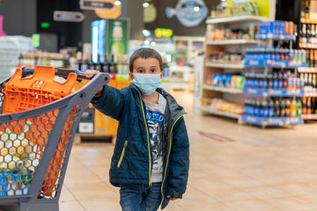 Boy wears protected mask in store. Shopping time during virus  outbreak. Boy in a medical mask. Shopping with kids during virus outbreak. Boy in face mask in supermarket.