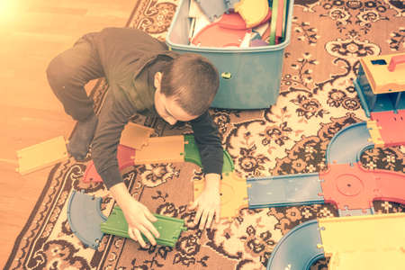charming boy plays on the floor with car track. Child playing with toys indoor. Activities for kids at home. toddler activities. Kindergarten boy at home during quarantine. toned