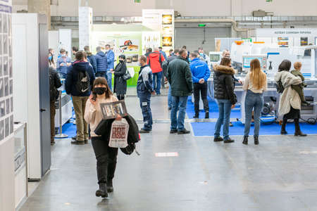 Kiev, Ukraine March 5 2021. Furniture exhibition during a pandemic. international furnishing accessories exhibition. People wearing medical masks during a pandemic. Exhibition and social distance 新闻类图片