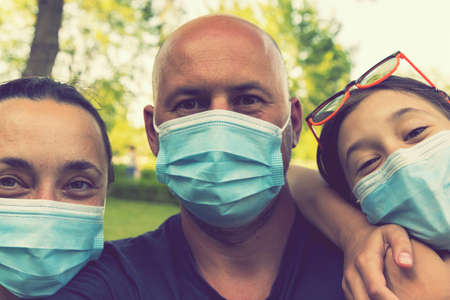 Family in protective medical masks. Mother, father, daughter protect themselves from the virus Coronavirus. Family in medical masks outdoors. close up. toned 免版税图像