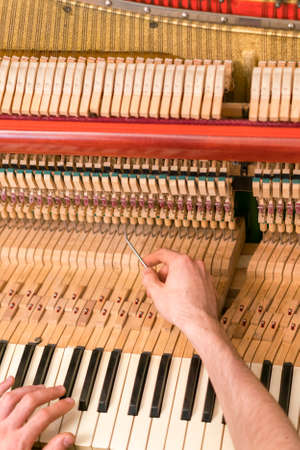 Piano tuning process. closeup of hand and tools of tuner working on grand piano. Detailed view of Upright Piano during a tuning. toned. vertical photo. toned 免版税图像