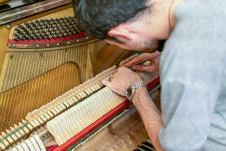 Piano tuning process. closeup of hand and tools of tuner working on grand piano. Detailed view of Upright Piano during a tuning
