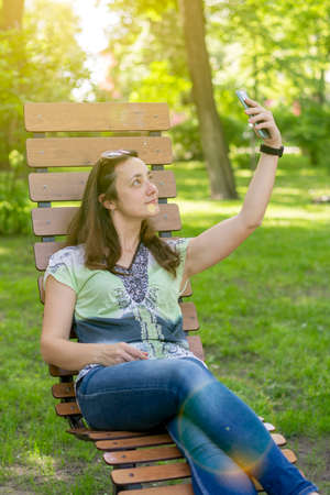 Young woman takes a selfie, sits on a bench in a city park. toned. vertical photo 免版税图像