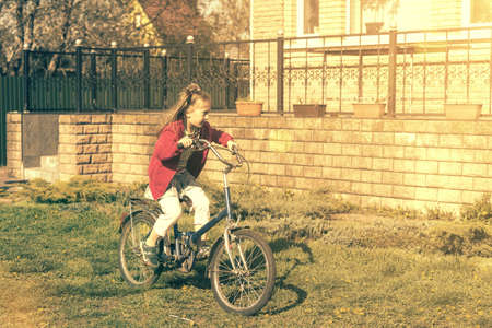 Girl riding a bike near the house. Girl on bicycle smiling while ride. Little girl enjoying bike ride on her way to school on warm summer day. toned