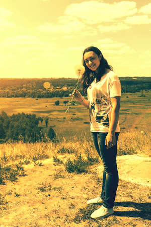 Happy, beautiful middle-aged woman with long hair on the background of a summer field. Healthy lifestyle and travel concept. Loneliness, unity with nature. toned