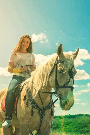 the rider on the white horse. Young horsewoman riding on white horse, outdoors view. girl on white horse runs free. vertical photo. toned