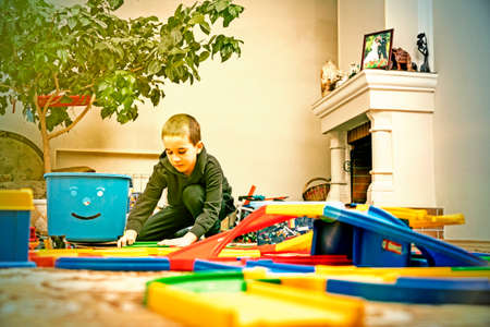 charming boy plays on the floor with car track. Child playing with toys indoor. Activities for kids at home. toddler activities. Kindergarten boy at home during quarantine. toned 免版税图像