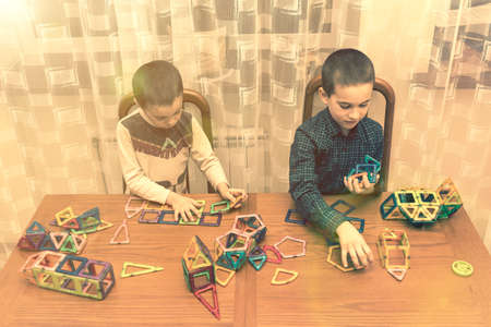 Children Boys playing with construction set on the floor.Educational games for kids. Boys playing whit blocks. Kindergarten. toned