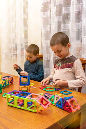 Children Boys playing with construction set on the floor.Educational games for kids. Boys playing whit blocks. Kindergarten. vertical photo. toned