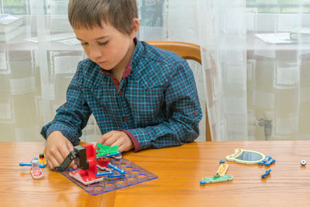 The boy playing an electric constructor. The child is played by intellectual toys. A boy in a blue shirt masters electronics. The concept of early development of children