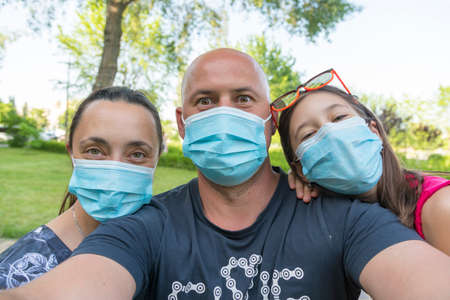 Family in protective medical masks. Mother, father, daughter protect themselves from the virus Coronavirus. Family in medical masks outdoors. close up